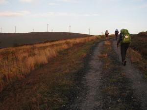 pilgerInnen auf dem weg zu anhöhe mit windrädern